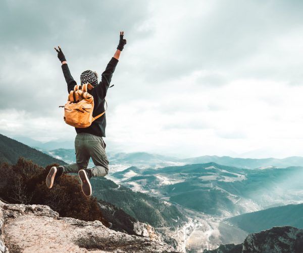 successful-hiker-man-jumping-on-the-top-of-the-mountain